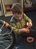 Older 3s using tools to work on bike